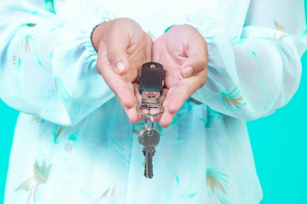 La jeune fille portait une chemise blanche à manches longues avec un motif de fleurs tenant un porte-clés avec un bleu. Photo gratuit