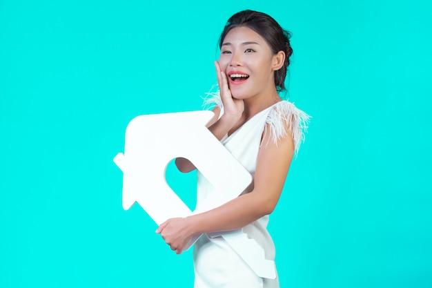 La jeune fille portait une chemise à manches longues blanche avec motif floral, tenant le symbole de la maison et montrant divers gestes en bleu. Photo gratuit