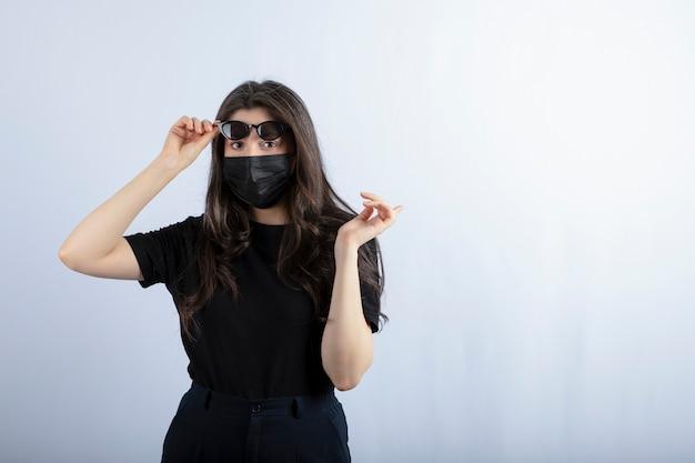 La Jeune Fille Porte Un Masque Noir En Raison De La Pandémie Et De La Pose. Photo gratuit