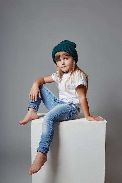 Jeune Fille Posant Sur Un Fond Gris, émotions Gaies Lumineuses Sur Le Visage De La Fille Photo Premium
