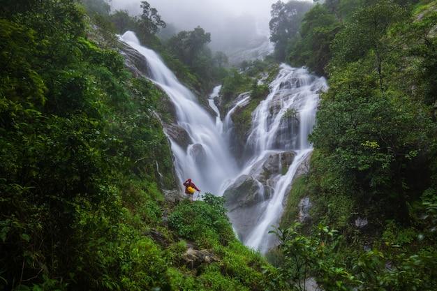 La jeune fille en pull rouge en tournée sur la cascade pi-tu-gro, belle cascade dans la province de tak, thaïlande. Photo Premium