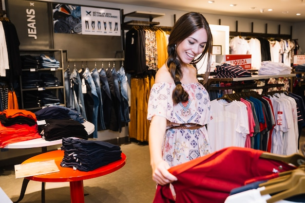 Jeune fille qui explore les vêtements dans la boutique Photo gratuit