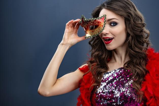 La jeune fille regarde la caméra avec un masque de carnaval Photo Premium