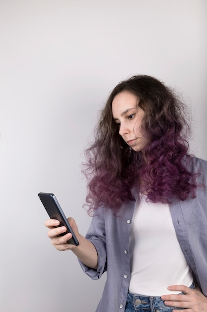 Jeune fille regarde pensivement dans le téléphone. couleur frisée colorant les cheveux mauves. gris Photo Premium