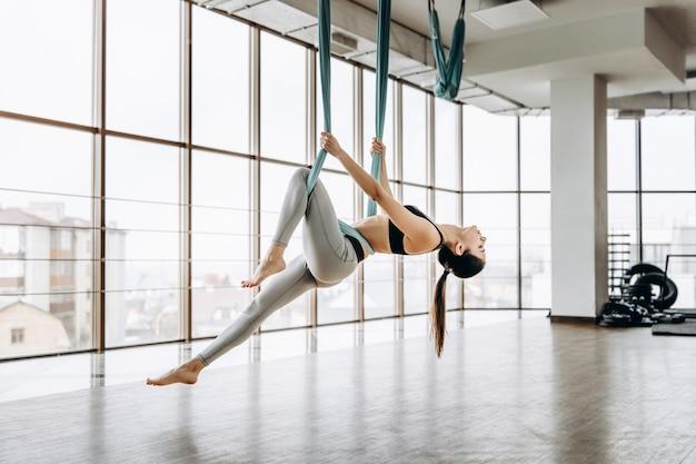 Jeune fille de remise en forme de corps assez mince pratiquant le yoga mouche dans la salle de gym. Photo Premium