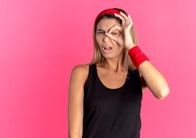 Jeune Fille De Remise En Forme En Sportswear Noir Et Bandeau Rouge Faisant Signe Ok Regardant La Caméra à Travers Ce Chanter Avec Une Expression De Confusion Debout Sur Un Mur Rose Photo gratuit