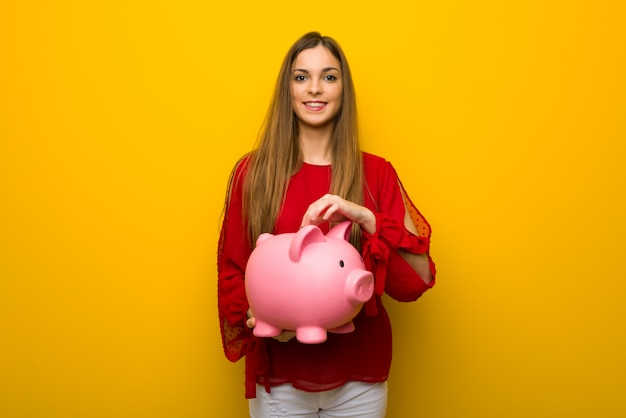 Jeune Fille Avec Une Robe Rouge Sur Un Mur Jaune Prenant Une Tirelire Et Heureuse Parce Qu'elle Est Pleine Photo Premium