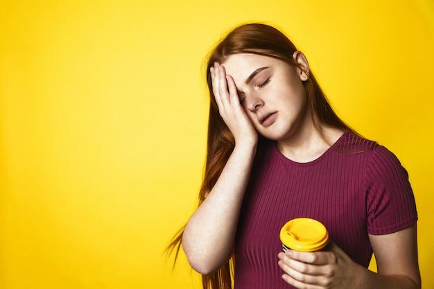 Jeune Fille Rousse Regarde Somnolent Et Tient Une Tasse Avec Du Café Debout Photo gratuit