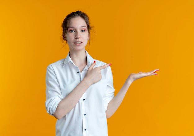 Jeune Fille Russe Blonde Anxieuse Pointe à Main Vide Isolé Sur Fond Orange Avec Copie Espace Photo gratuit