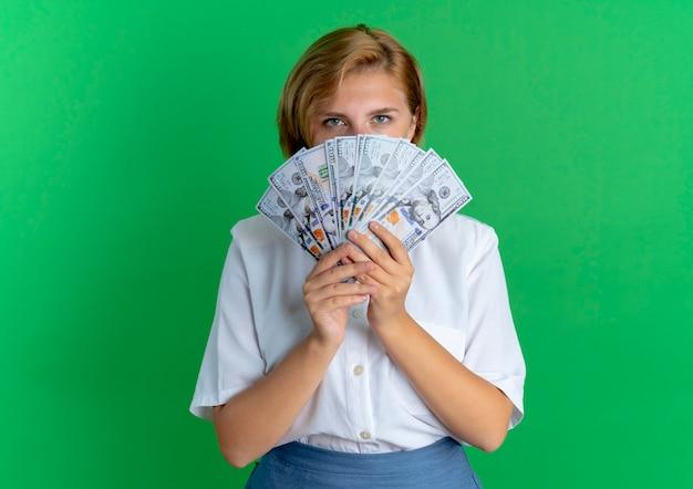 Jeune Fille Russe Blonde Confiante Regarde L'argent Isolé Sur Fond Vert Avec Copie Espace Photo gratuit