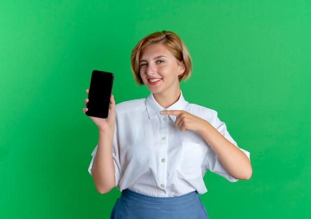 Jeune Fille Russe Blonde Souriante Points Au Téléphone Isolé Sur Fond Vert Avec Espace Copie Photo gratuit