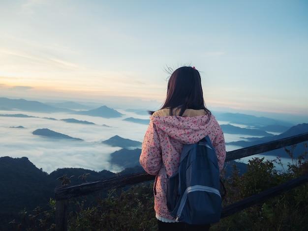 Jeune fille avec sac à dos, appréciant le lever du soleil sur le sommet de la montagne. Photo Premium
