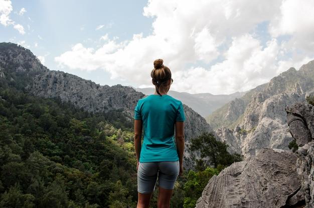Jeune fille se dresse au sommet de la montagne Photo Premium