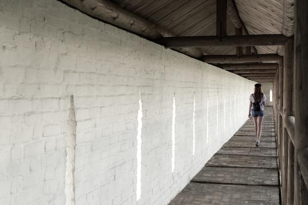 La jeune fille se promène dans la longue allée du monastère sur le fond d'un mur blanc. Photo Premium
