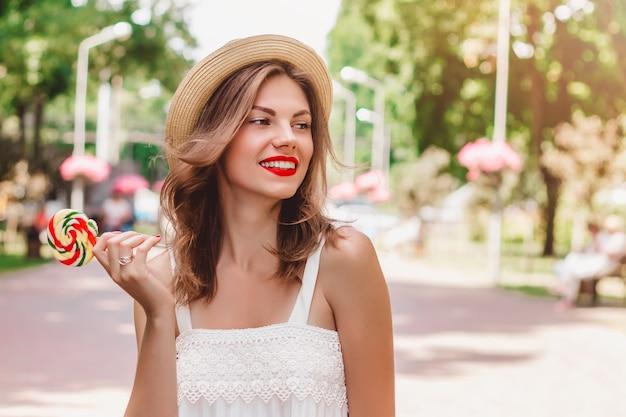 Une jeune fille se promène dans le parc et tient dans ses mains une sucette multicolore de forme ronde Photo Premium