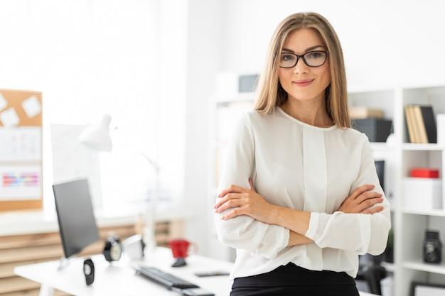 Une Jeune Fille Se Tient Penchée Sur Une Table Dans Le Bureau. Photo Premium