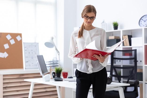 Une jeune fille se tient près d'un bureau d'ordinateur et fait défiler un dossier contenant des documents. Photo Premium