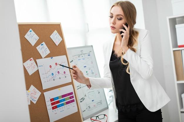 Une jeune fille se tient près du tableau avec des autocollants, parle au téléphone et tient un crayon à la main. Photo Premium