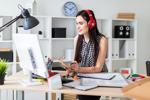 Une jeune fille se tient près d'une table, tient une figure humaine en bois et un marqueur vert dans ses mains et regarde l'écran. avant la fille sur la table se trouve un tableau magnétique. Photo Premium