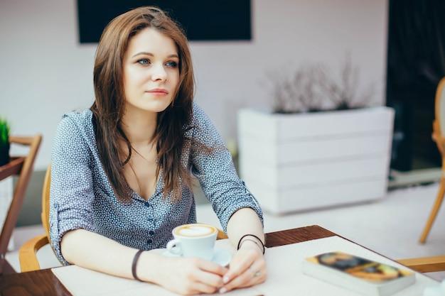 Jeune fille séduisante boit du café dans un café de la ville. Photo Premium