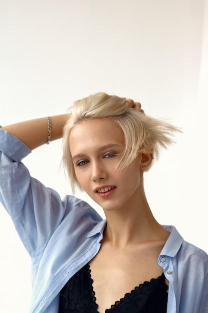 Jeune fille séduisante élégante en tenue décontractée touche ses cheveux volants. Photo Premium
