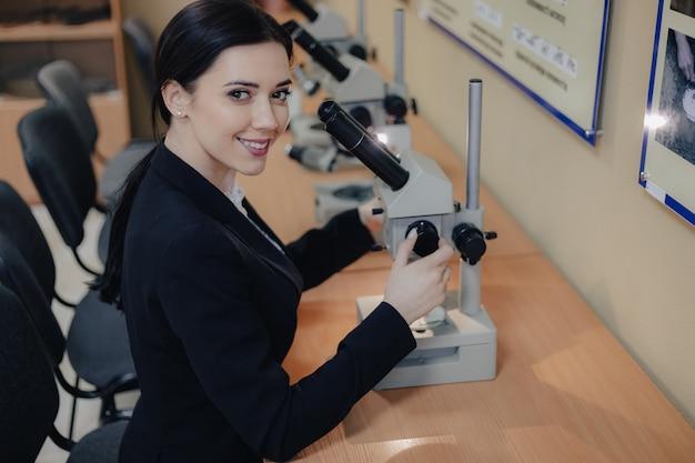 Jeune fille séduisante émotionnelle assis à la table et travaillant avec un microscope dans un bureau moderne ou un public Photo Premium