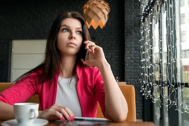 Jeune fille séduisante, femme d'affaires, parler au téléphone portable assis seul dans un café Photo Premium