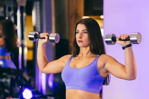 Jeune Fille Sexy Effectue Des Exercices Sportifs Avec Des Haltères Dans La Salle De Gym. En Vêtements Bleus Photo Premium