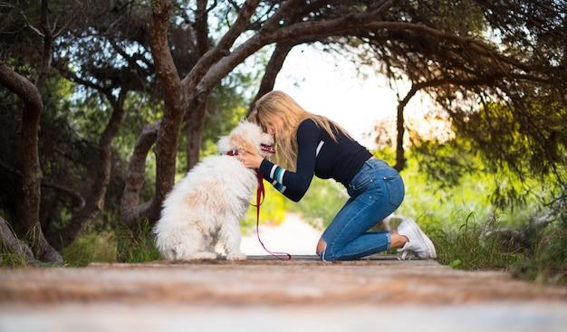 Jeune fille avec son chien dans un parc Photo Premium