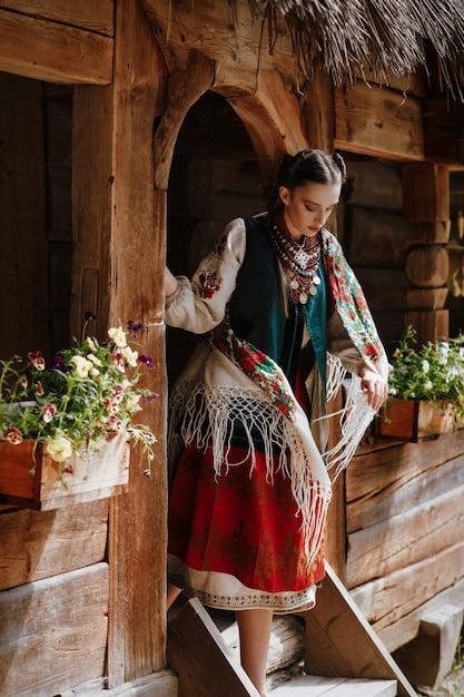 Jeune fille sort de la maison dans une robe ukrainienne traditionnelle Photo gratuit