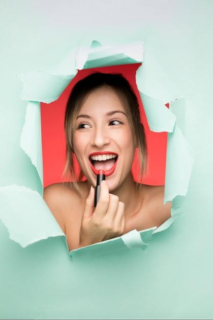 Jeune fille souriante à l'aide de rouge à lèvres Photo gratuit