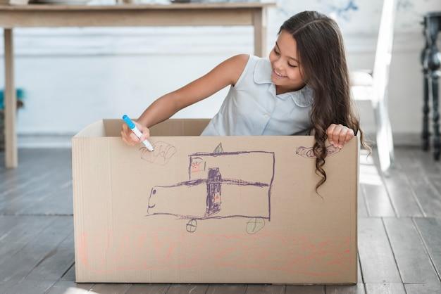 Jeune fille souriante assise à l'intérieur de la boîte en carton, dessin au marqueur Photo gratuit