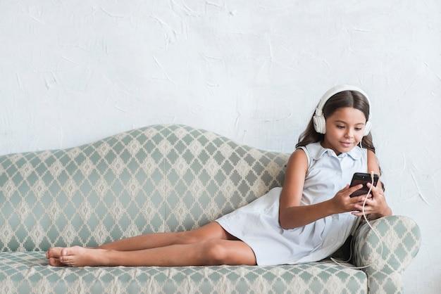 Jeune fille souriante avec un casque sur la tête en regardant un téléphone mobile Photo gratuit