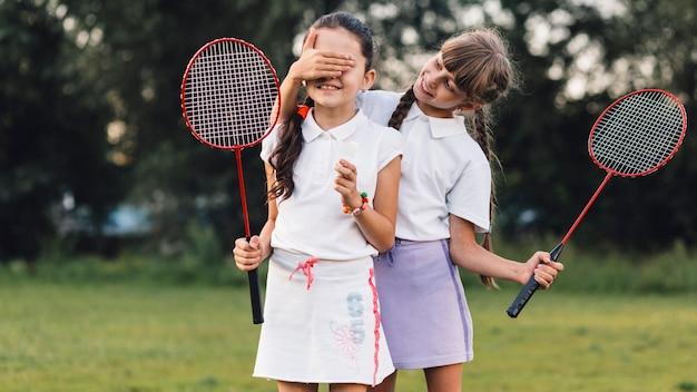 Jeune fille souriante couvrant ses yeux d'ami tenant du badminton Photo gratuit