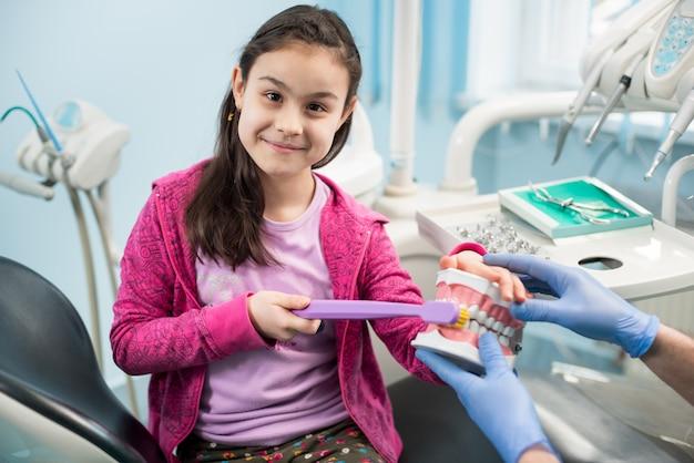 Jeune Fille Souriante Dans Une Chaise De Dentiste Montrant Un Brossage Des Dents Approprié à L'aide D'un Modèle De Mâchoire Dentaire Et D'une Grande Brosse à Dents Dans Un Cabinet Dentaire Photo Premium