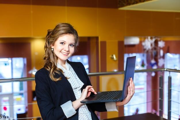 Jeune fille souriante, debout dans un café et travaillant sur un ordinateur portable Photo Premium