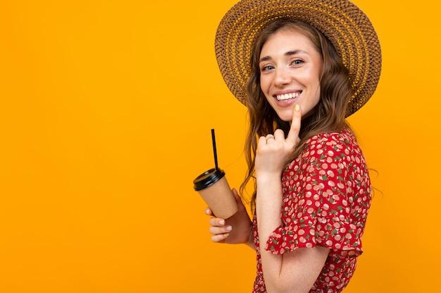 Jeune Fille Souriante Avec Du Café Sur Fond Jaune Dans Une Robe Rouge Photo Premium
