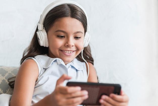 Jeune fille souriante écoute de la musique sur le casque à l'aide d'un téléphone intelligent Photo gratuit