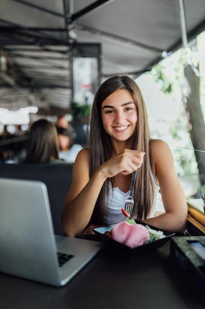 Jeune Fille Souriante Est Assise Dans Un Café Et Travaille Sur Ses Devoirs Sur Un Ordinateur Portable Pendant La Journée Photo gratuit