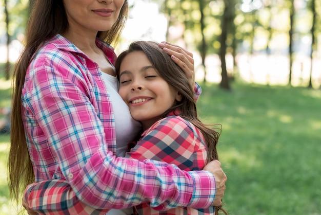 Jeune fille souriante étreignant sa mère avec les yeux fermés dans le jardin Photo gratuit