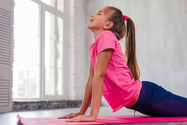 Jeune fille souriante exerçant près de la fenêtre Photo gratuit