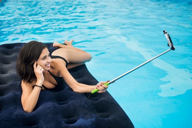 Jeune fille souriante et fait une photo de selfie au téléphone avec un bâton de selfie sur un matelas dans la piscine du resort Photo Premium
