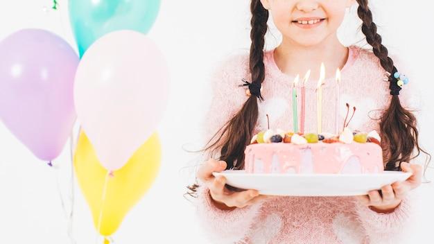 Jeune fille souriante avec un gâteau d'anniversaire Photo gratuit