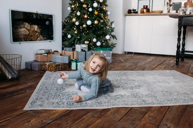 Jeune fille souriante jouant avec une décoration de noël Photo Premium