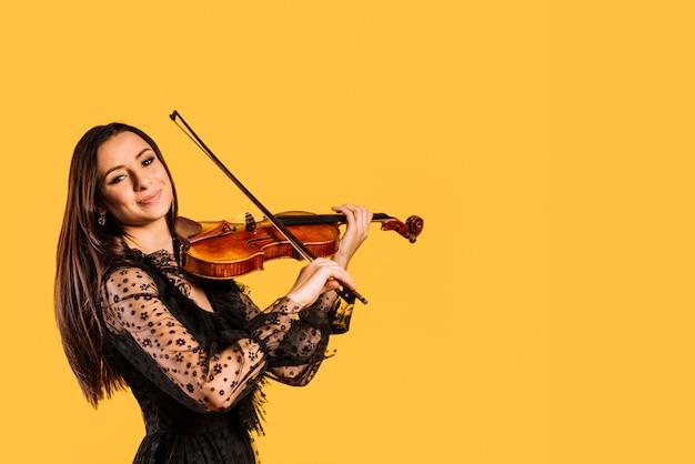 Jeune fille souriante jouant du violon Photo gratuit