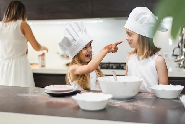 Jeune fille souriante pointant sa sœur avec les mains en désordre dans la cuisine Photo gratuit