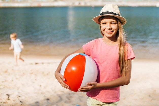 Jeune Fille Souriante Portant Le Ballon De Plage à Deux Mains Photo gratuit