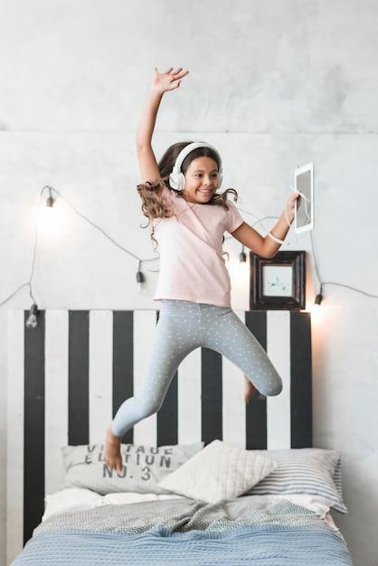 Jeune fille souriante portant un casque sautant par-dessus le lit avec tablette numérique Photo gratuit
