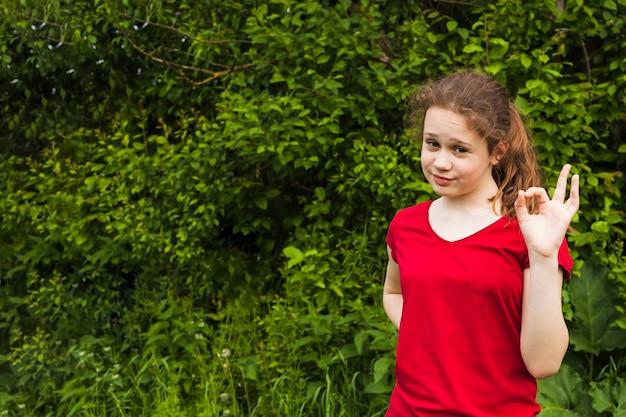 Jeune fille souriante posant et montrant un geste correct dans le parc Photo gratuit