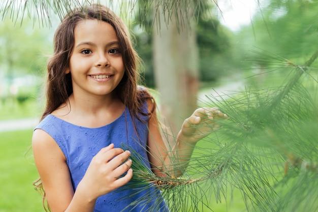 Jeune fille souriante qui pose dans la nature Photo gratuit